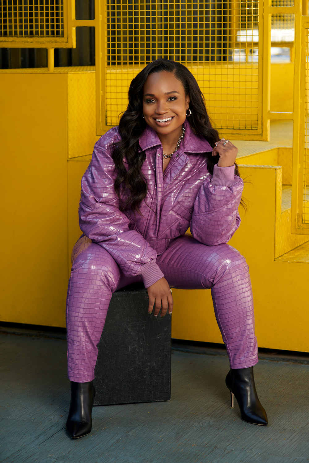 Kayla Grey in a purple outfit sitting in front of a yellow staircase