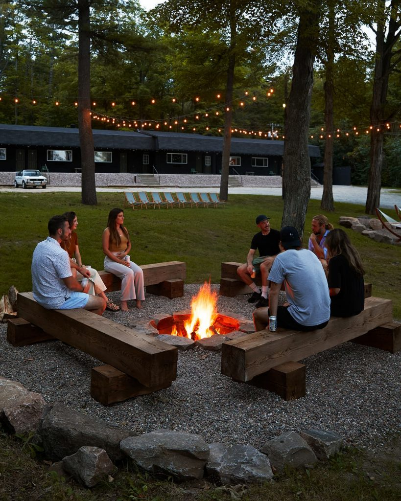 Guests congregate around a fire pit at Somewhere Inn Calabogie